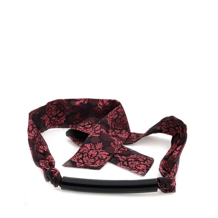 Silikonowy knebel na zmysłowej, czarno-czerwonej tkaninie o subtelnym połysku